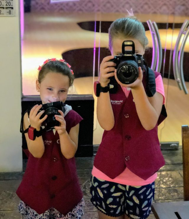 Two kids holding cameras pointed at the camera.
