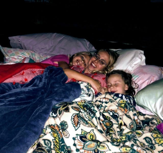 Mom and two daughters covered in blankets laying on pillows sleeping in a backyard.