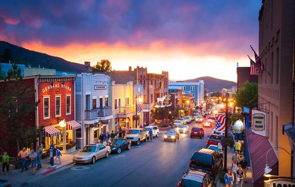 Sun setting on Main Street Park City, Utah. Lights on the building and cars on the road. Best road trip stop.