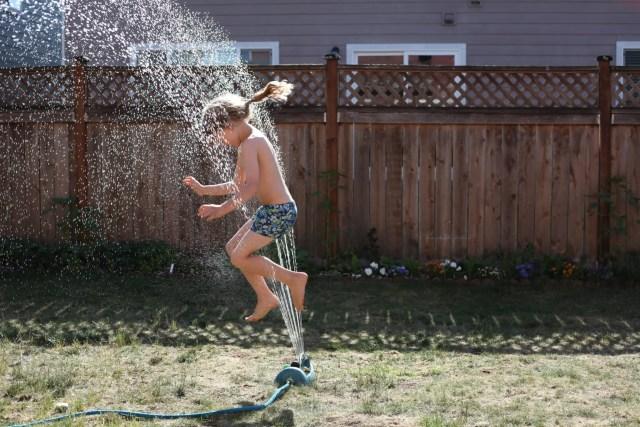 Little girl jumping through a sprinkler in a backyard.
