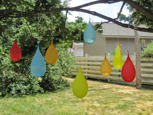 Colorful water balloons hanging from a tree to show water balloon pintatas.