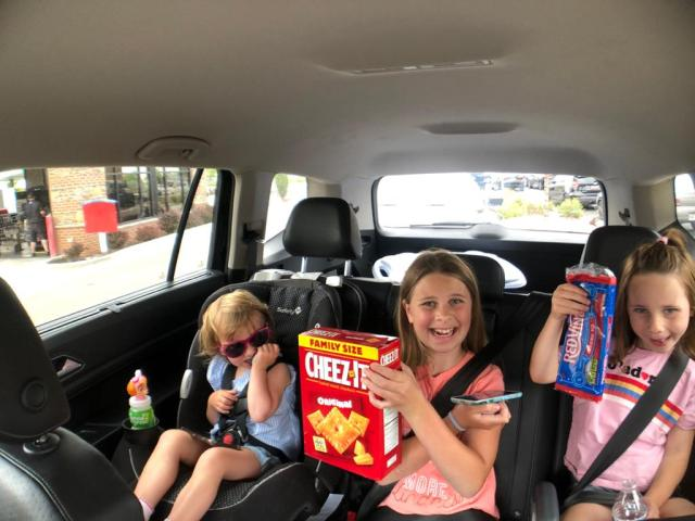 3 kids in the backseat of a car holding up road trip snacks.