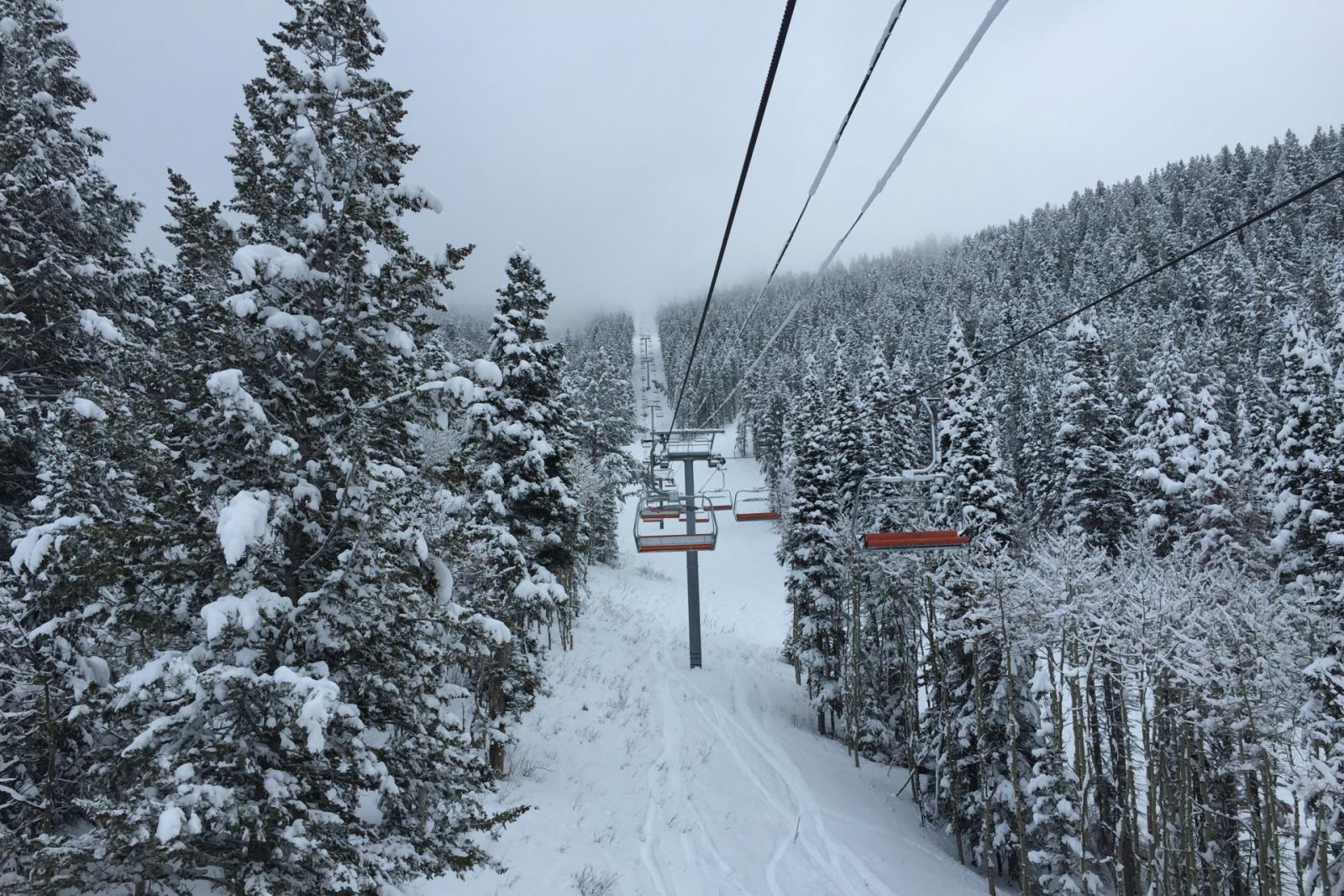 Ski lifts going up a snowy mountain