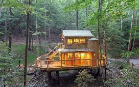 Large cabin with all inside lights in the middle of the forest.