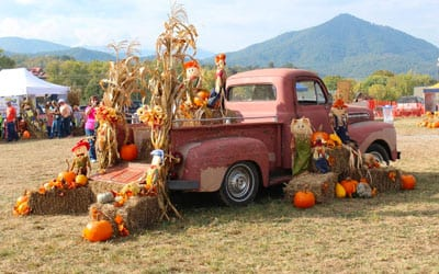 Old red truck decorated with pumpkin and hay for fall.