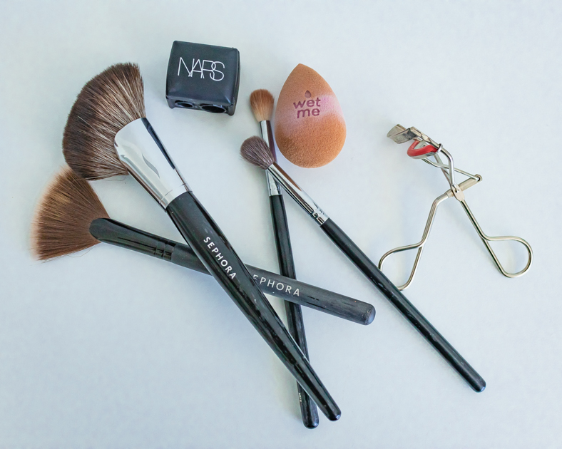 tools to pack like highlighter brush, beauty blender, eyelash curler travel makeup essentials for your trip