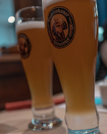 Picture of two German beers on a table. One of the things to do with one day in Munich is drink German beer.