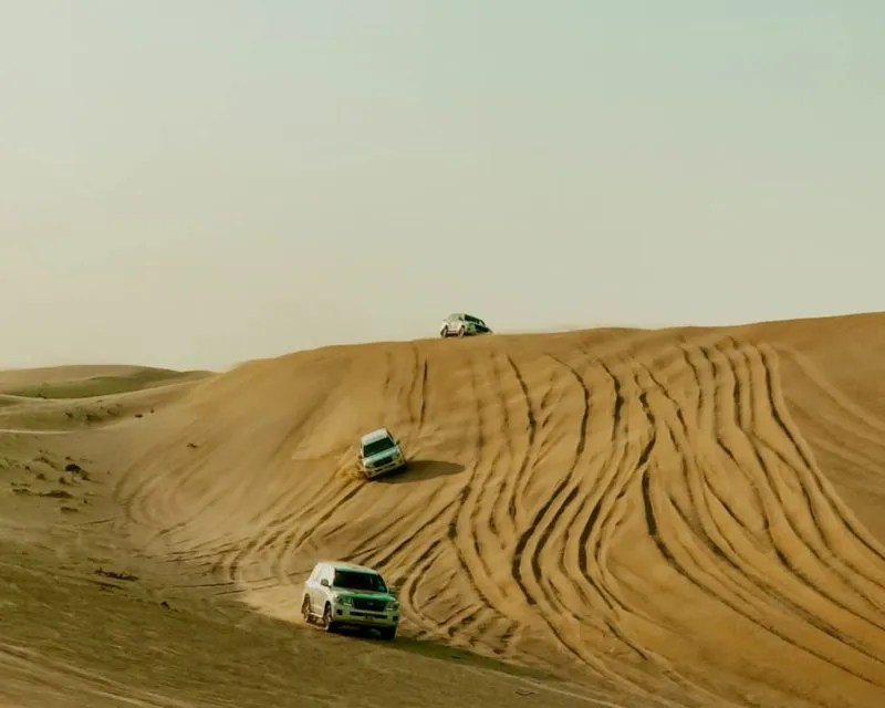 3 cars going down a sand dune during my Abu Dhabi day trip from Dubai