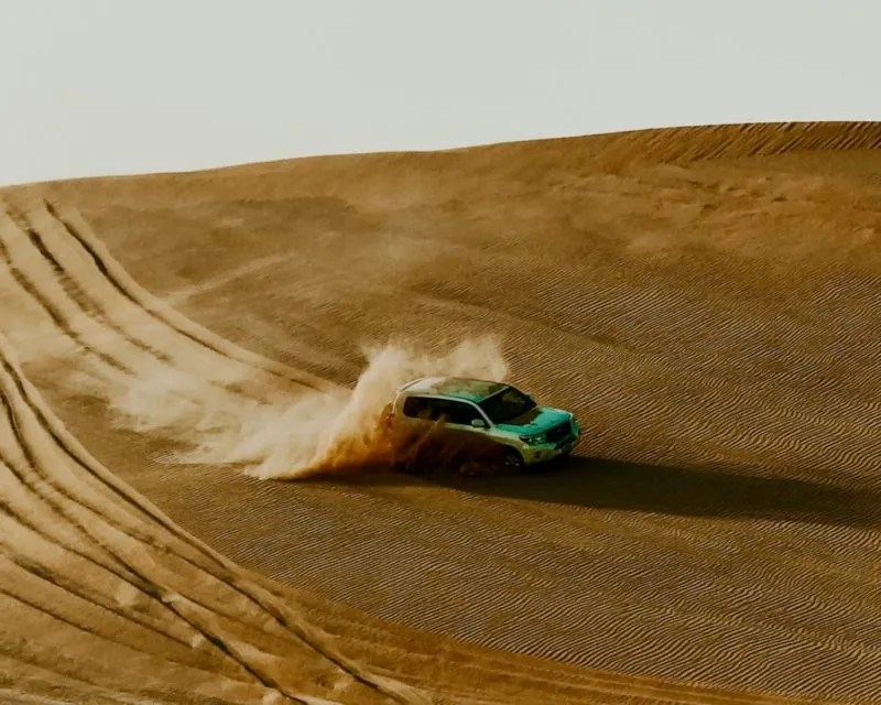 car going down a sand dune in the Abu Dhabi desert
