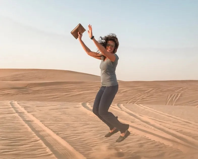 Me jumping in the desert in Abu Dhabi a top solo female travel destinations