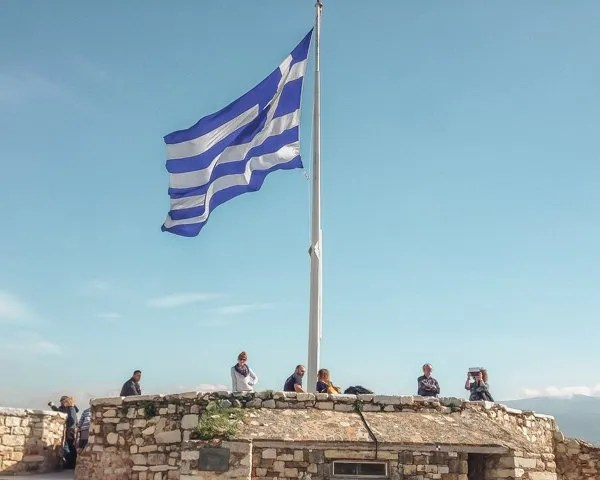 Picture of the Greek flag at the Acropolis one of the things to do in Athens, Greece