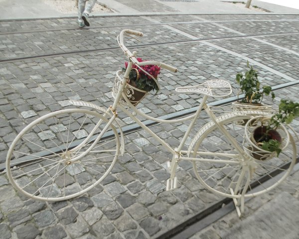 Picture of a bike with potted plants on the winding street in Plaka