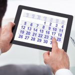 Businessman Looking At Calendar On Digital Tablet