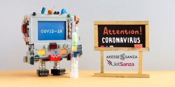 Attention coronavirus covid 19. A robotic research computer doctor holds a test tube with drugs and pills. Black chalkboard with the handwritten words warning of an epidemiological virus threat.