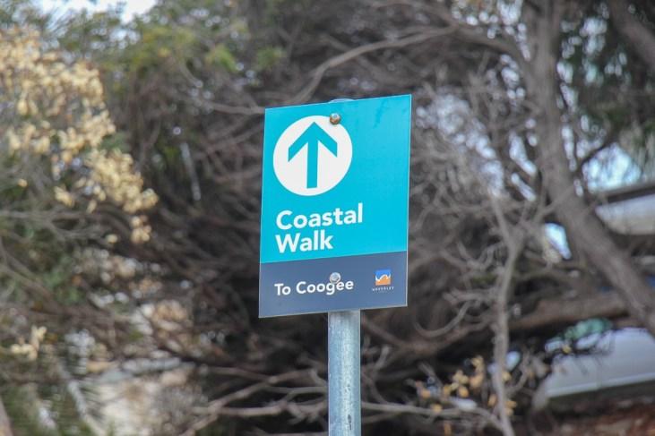 Bondi to Coogee Coastal Walk sign post on trail near Sydney, Australia