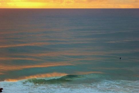 A lone surfer at Sunrise in Coolangatta, Gold Coast, Australia