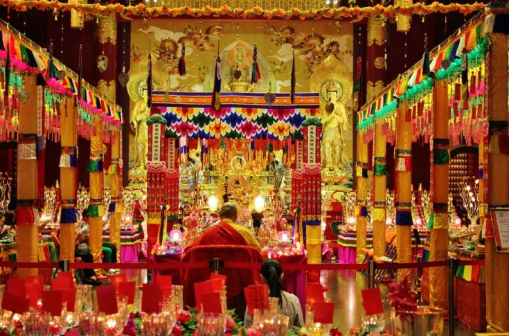 Monks chanting inside Buddha Tooth Relic Temple in Chinatown, Singapore