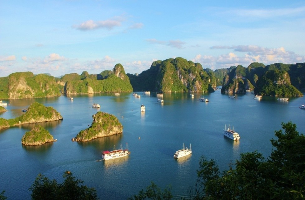 Karst islands and junk boats dot Halong Bay in the late afternoon in Vietnam
