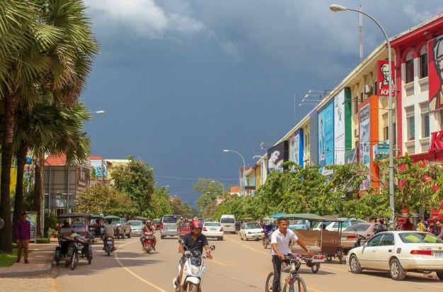 Motos, bicycles and tuk tuks on city street in Siem Reap, Cambodia