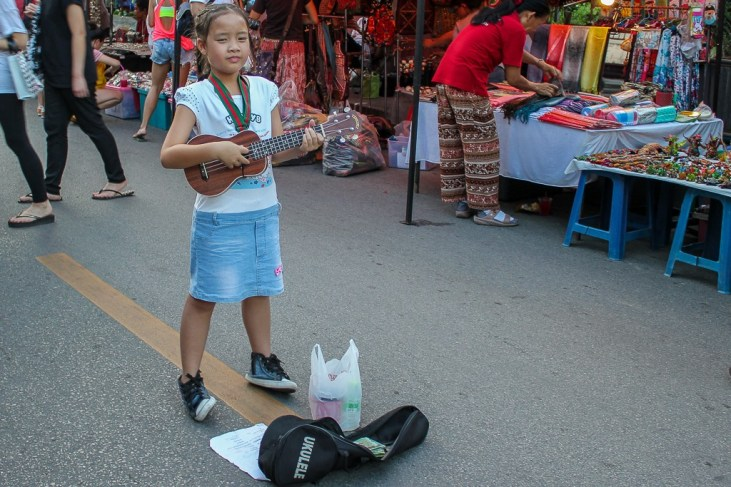 Young girl sings for tips at Saturday Night Market in Chiang Mai, Thailand