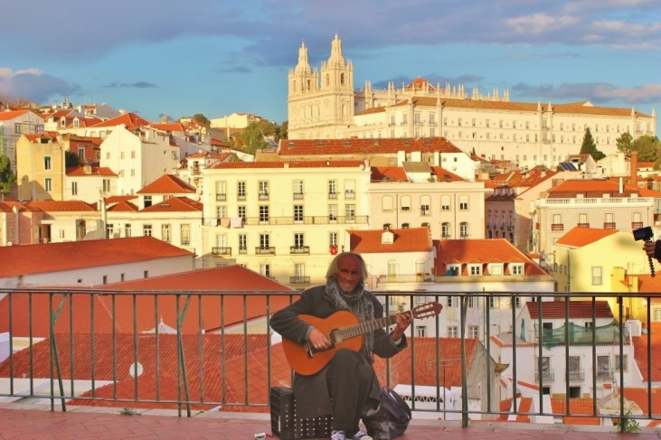 Man strums guitar at Portas do Sol Miradouro in Lisbon, Portugal