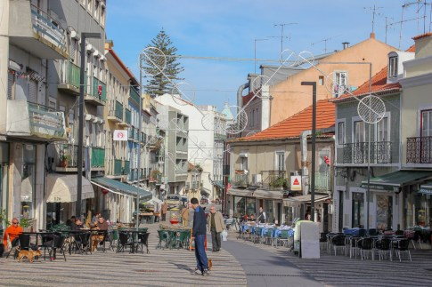 Main street in Cacilhas lined with cafes near Lisbon, Portugal
