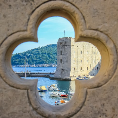 Peering through a hole in the bridge to Old Port in Dubrovnik, Croatia