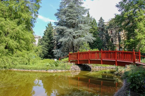 Red footbridge crosses pond in Botanical Garden in Zagreb, Croatia