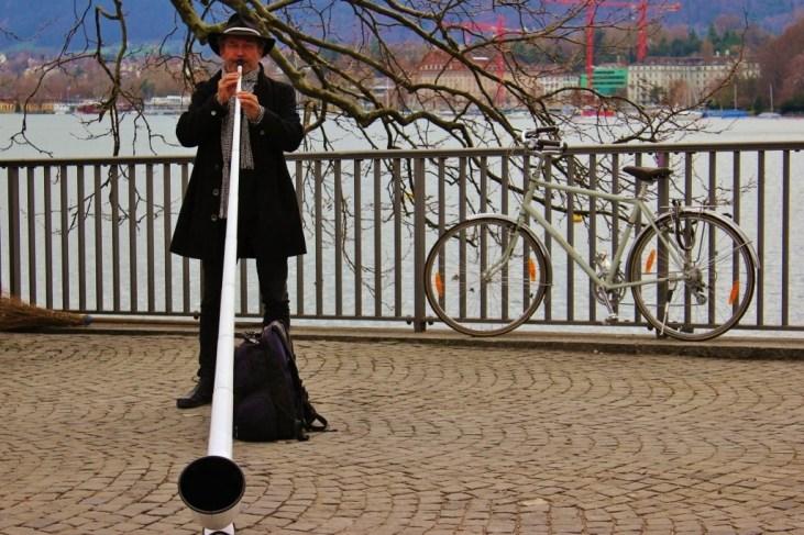 Man plays the alphorn on Lake Zurich, Zurich, Switzerland JetSettingFools.com