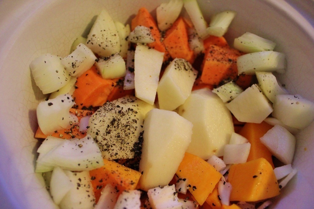 The second step to make pumpkin soup is to peel and cube both potatoes and chop onion and place in crock pot. Make two cups of broth with stock cubes and pour into crock pot. Add pepper to liking.