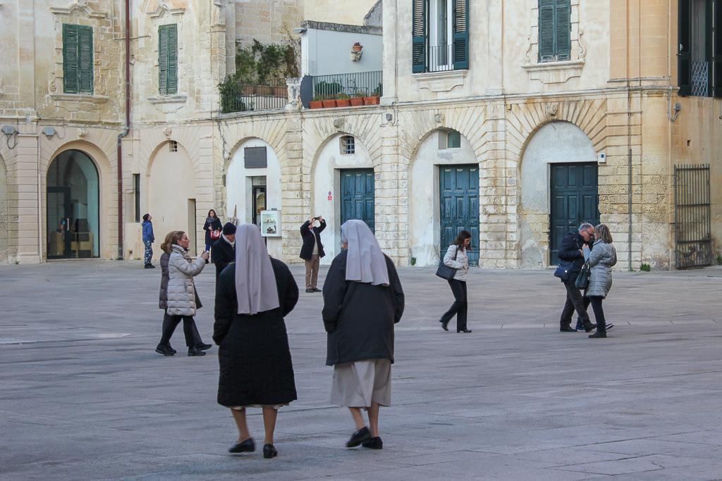 Two nuns cross plaza in Piazza del Duomo in Lecce, Italy