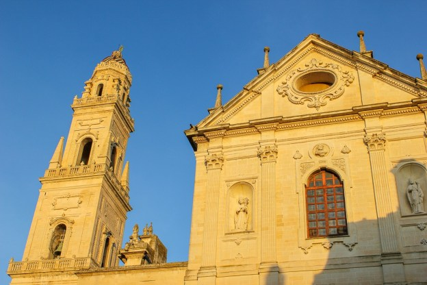 Late afternoon sun shines on bell tower and church in Piazza del Duomo in Lecce, Italy
