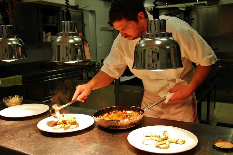 Chef preparing plates of baked octopus at Proteus Restaurant, Postojna Cave, Slovenia