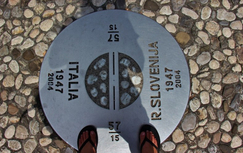 Standing in two countries at once on the border marker between Italy and Slovenia Europe Square