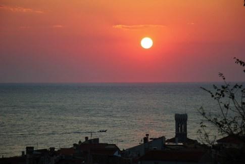 Round sun at sunset off point of Piran, Slovenia