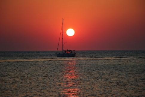 Orange ball sun at sunset with sailboat, Piran Slovenia
