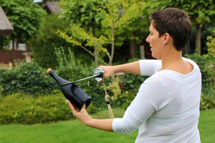 Opening a bottle of sparkling Slovenian wine at Hisa Vina Cuk