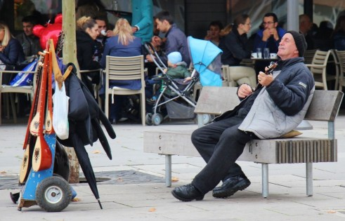 Man plays traditional instrument on Mother Teresa Boulevard in Prishtina, Kosovo