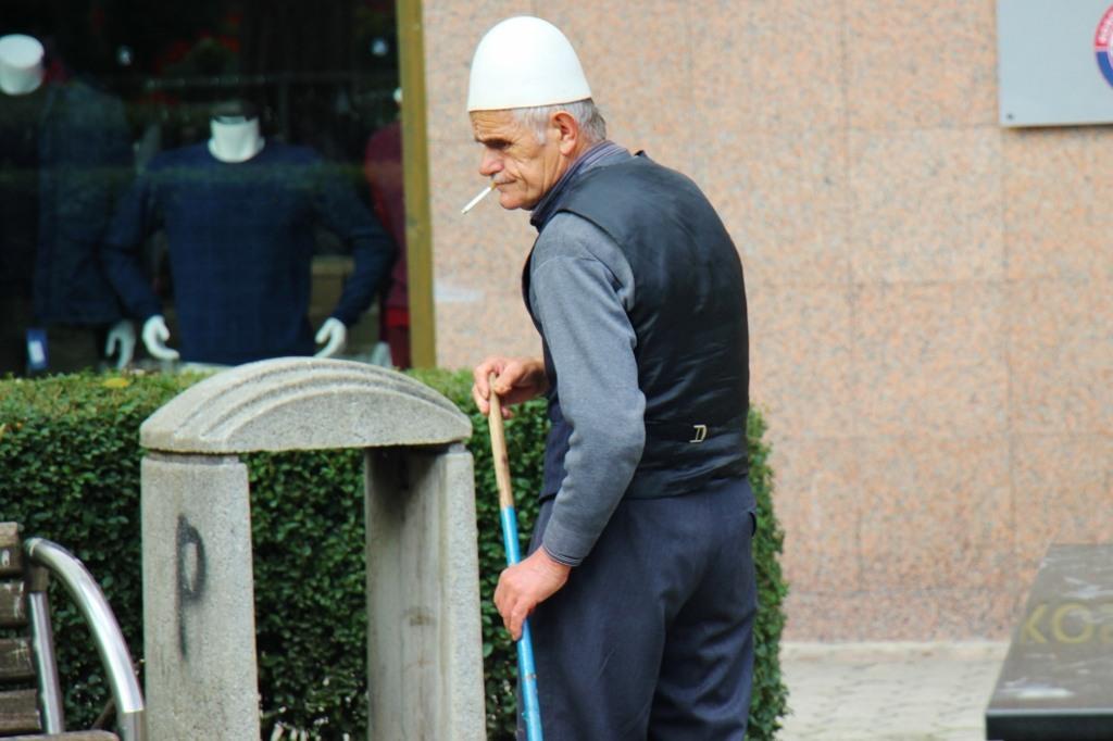 Old man wearing plis smokes cigarette and sweeps sidewalk
