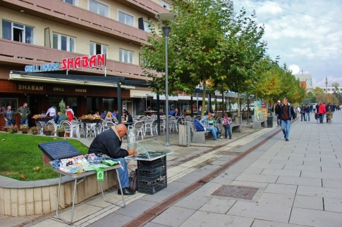 Street Seller sets up table on Mother Teresa Boulevard in Prishtina, Kosovo