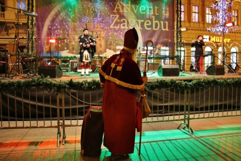 Father Christmas watches bagpipe performance on Ban Jelacic Square during Christmas in Zagreb, Croatia