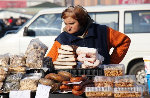 Woman sells fresh meat products at Autopija flea market in Osijek, Croatia