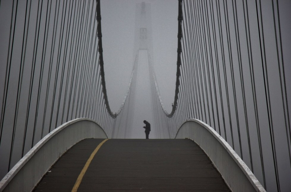 Man stands on pedestrian bridge on foggy morning in Osijek, Croatia