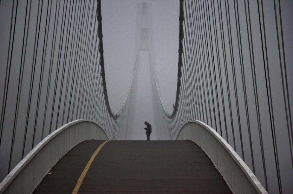 Man stands on pedestrian bridge on foggy morning in Osijek, Croatia