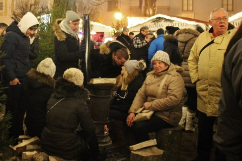 Staying warm by wood-burning stoves at Advent u Tvrdi in Osijek, Croatia