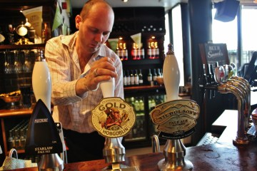 Bartender pouring Cask Ale at pub in London, England, jetsettingfools.com