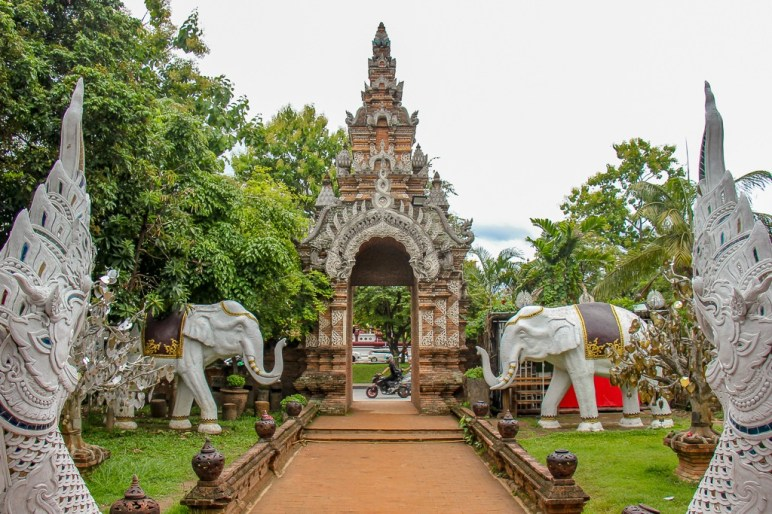 Elephant sculptures guard ornate gate at Lok Moli Temple in Chiang Mai, Thailand