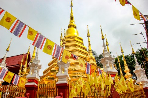 Large golden stupa surrounded by flags at Wat Phan Tao in Chiang Mai, Thailand