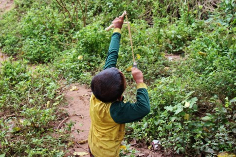 Boy uses slingshot in Ban Kok Eak Village, Laos
