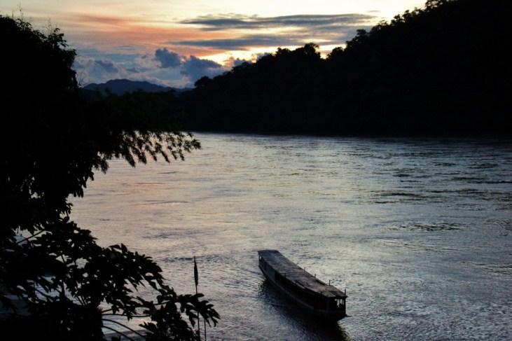 River boat heads upstream at sunset on Mekong River in Luang Prabang, Laos